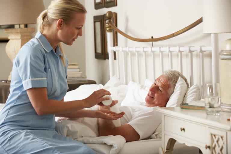 Infermiera che aiuta un uomo costretto a letto a prendere le medicine