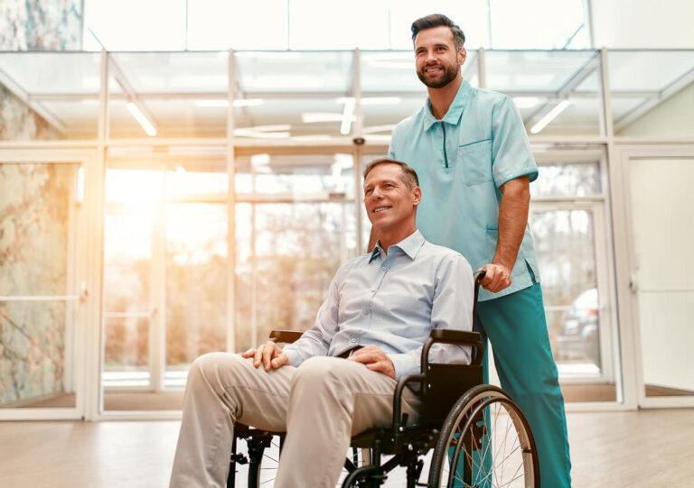 Infermiere che aiuta un uomo su una sedia a rotelle che lascia un ospedale