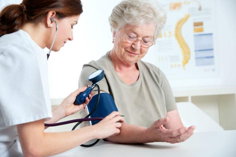 Medico che prende la pressione del sangue a una signora anziana