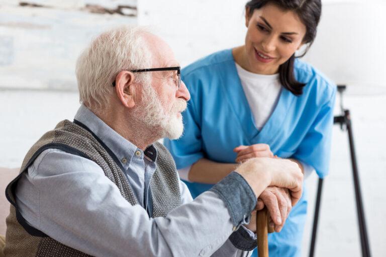 Infermiera che aiuta un anziano