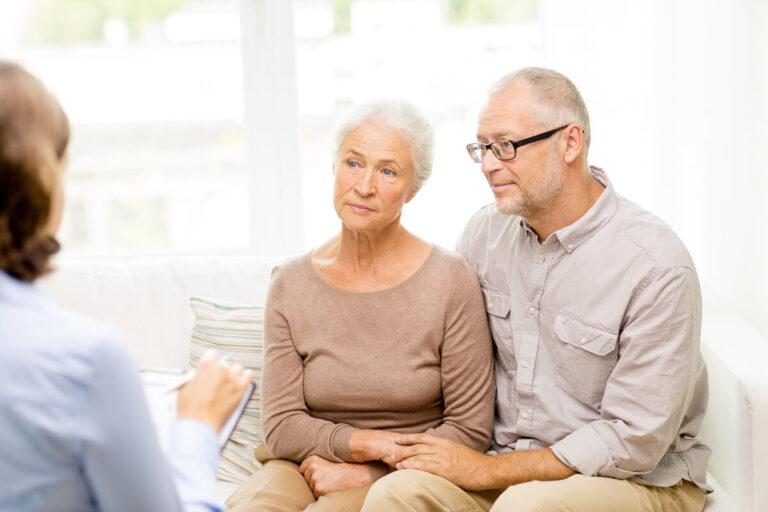 Coppia di anziani che ascolta un assistente sociale