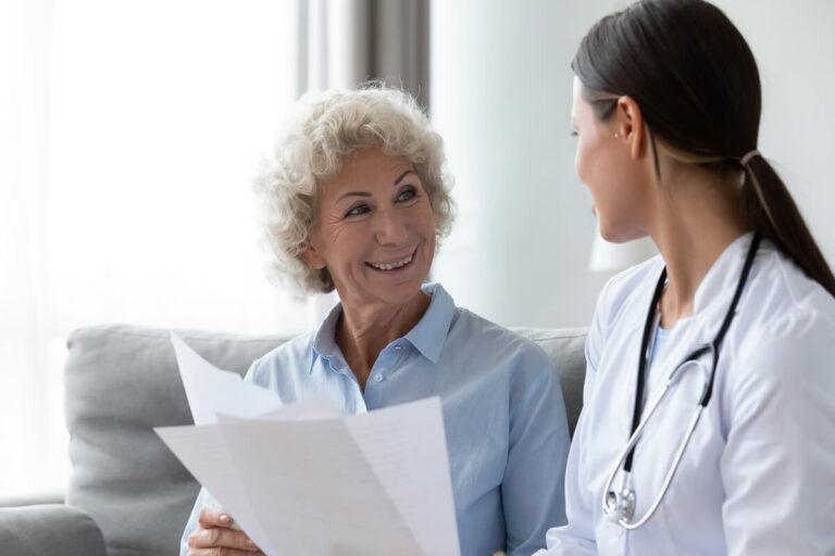 Signora sorridente che scambia documenti con un giovane medico